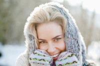 Close up portrait of smiling woman wearing fur hood and mittens