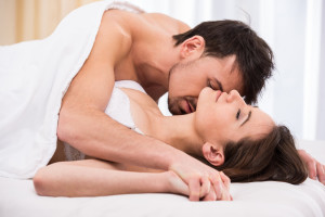 Young love couple in bed, romantic scene in bedroom.